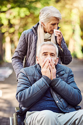 Buy stock photo Cropped portrait of a wheelchair-bound senior man and his wife blowing their noses while out at the park