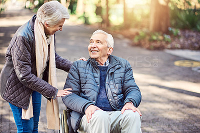 Buy stock photo Cropped shot of a wheelchair-bound senior man spending the day with his wife in the park