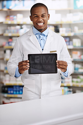Buy stock photo Portrait of a young pharmacist holding up a digital tablet with a blank screen in a chemist