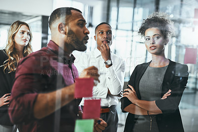 Buy stock photo Shot of businesspeople brainstorming in a Shot of a group of young businesspeople brainstorming in a modern office office