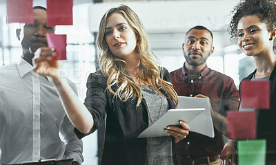 Buy stock photo Shot of a group of young businesspeople brainstorming in a modern office