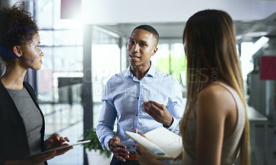 Buy stock photo Shot of a group of young businesspeople having discussion in a modern office
