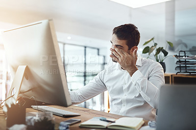 Buy stock photo Shot of a young businessman looking stressed out and tired while working in an office