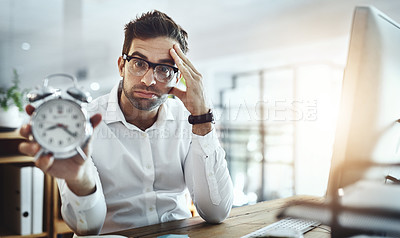 Buy stock photo Portrait of a young businessman looking stressed out while holding a clock in an office