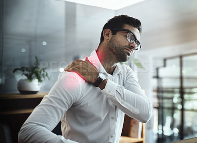 Buy stock photo Shot of a young businessman suffering with shoulder pain while working in an office