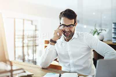 Buy stock photo Shot of a young businessman talking on a cellphone while working in an office