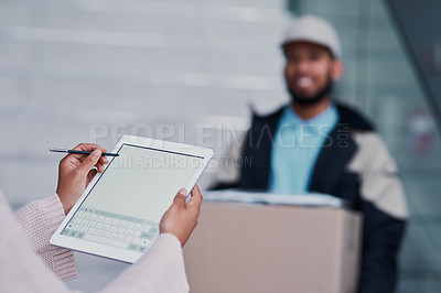 Buy stock photo Cropped shot of a young man making a delivery while an unrecognizable female customer signs on a tablet
