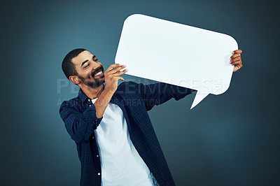 Buy stock photo Studio shot of a man holding a speech bubble against a gray background