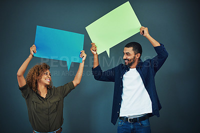 Buy stock photo Studio shot of a young couple holding speech bubbles against a gray background
