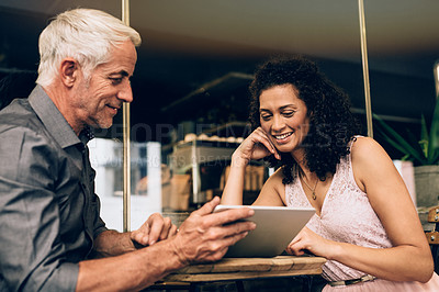 Buy stock photo Shot of a mature couple using a digital tablet together on a coffee date