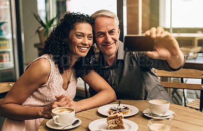 Buy stock photo Shot of a mature couple taking a selfie on a coffee date