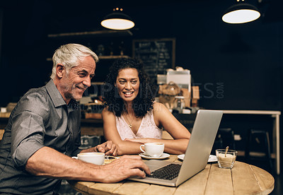 Buy stock photo Shot of a mature couple using a laptop together on a coffee date