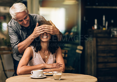 Buy stock photo Shot of a mature man covering his wife's eyes on a coffee date