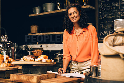 Buy stock photo Portrait of a mature woman going over paperwork while working in a coffee shop