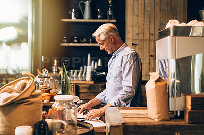 Buy stock photo Shot of a mature man going over paperwork while working in a coffee shop