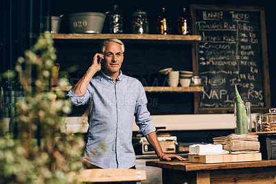 Buy stock photo Shot of a mature man using a mobile phone while working in a coffee shop