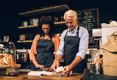 Buy stock photo Shot of a mature man and woman going over paperwork while working in a coffee shop