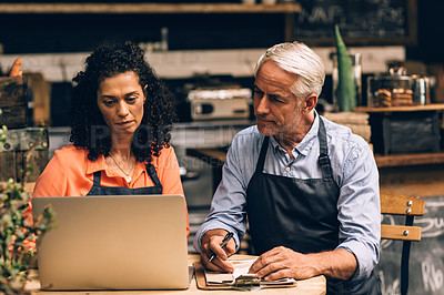 Buy stock photo Shot of a confident mature man and woman using a laptop while working in a coffee shop