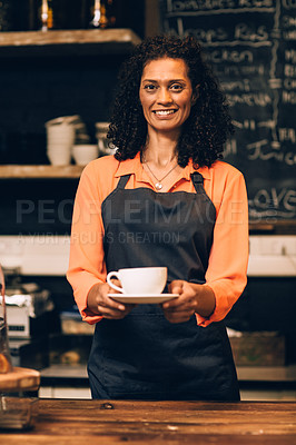 Buy stock photo Portrait of a mature woman serving a cup of coffee in a coffee shop