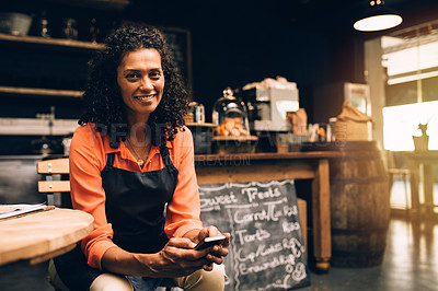 Buy stock photo Portrait of a mature woman using a mobile phone while working in a coffee shop