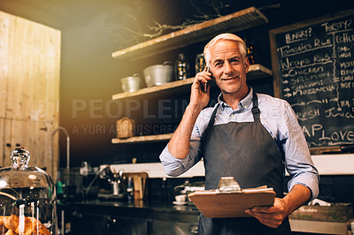 Buy stock photo Portrait of a mature man using a mobile phone while working in a coffee shop