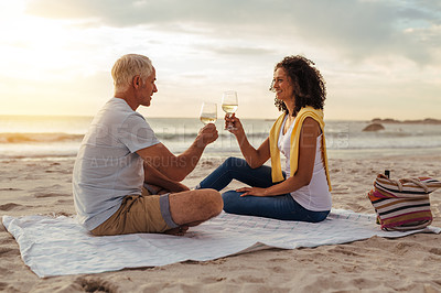 Buy stock photo Shot of a mature couple having drinks on a romantic date at the beach