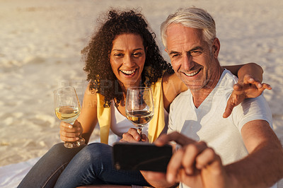 Buy stock photo Shot of a mature couple taking a selfie while enjoying drinks at the beach