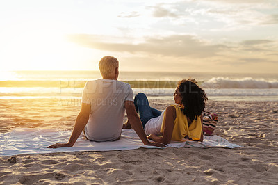 Buy stock photo Shot of a mature couple watching the sunset together at the beach