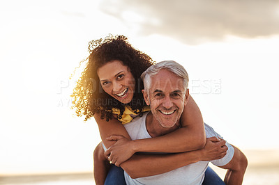 Buy stock photo Portrait of a mature couple enjoying a piggyback ride at the beach