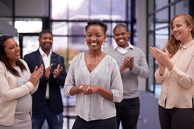 Buy stock photo Shot of a young businesswoman being applauded by her colleagues in a modern office
