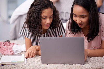 Buy stock photo Shot of two teenage girls using a laptop together at home