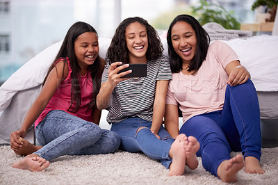 Buy stock photo Shot of three teenage girls taking a selfie together at home