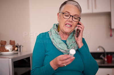 Buy stock photo Shot of a senior woman reading the label on a medicine container and talking on a cellphone