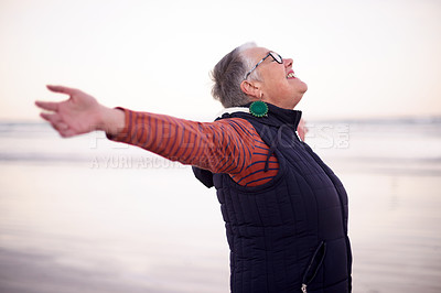 Buy stock photo Shot of a happy senior woman enjoying a day at the beach