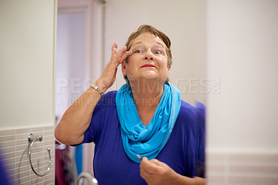 Buy stock photo Shot of senior woman going through her beauty routine in the bathroom