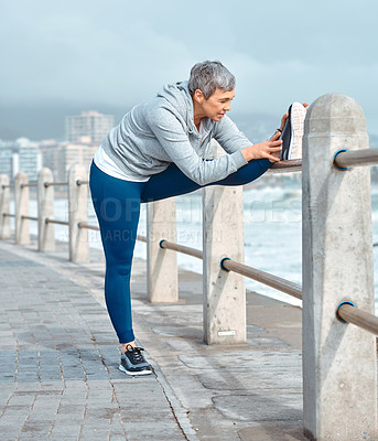 Buy stock photo Shot of a mature woman stretching her legs before a run outdoors