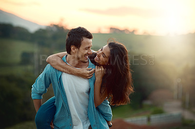 Buy stock photo Cropped shot of a handsome young man piggybacking his girlfriend while spending some time outdoors