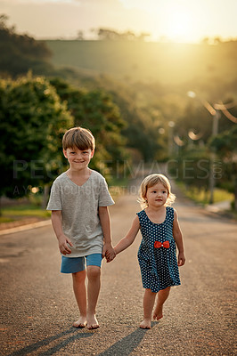 Buy stock photo Shot of an adorable little boy walking hand in hand with his sister down the road in the neighbourhood