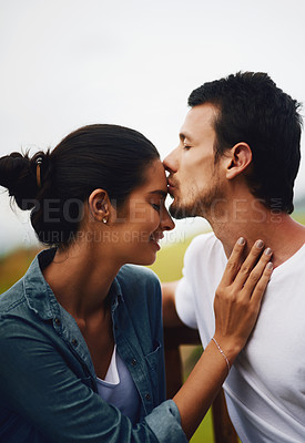 Buy stock photo Shot of an affectionate young couple spending a romantic day in the park