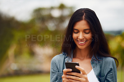 Buy stock photo Shot of an attractive young woman using a mobile phone in a park