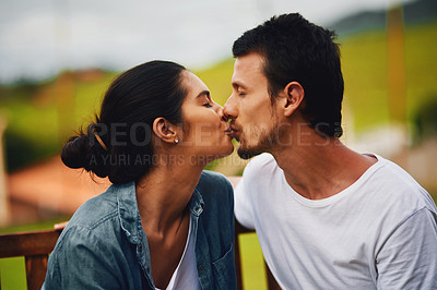 Buy stock photo Shot of an affectionate young couple kissing in the park