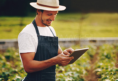 Buy stock photo Shot of a young man using a digital tablet while working in a garden