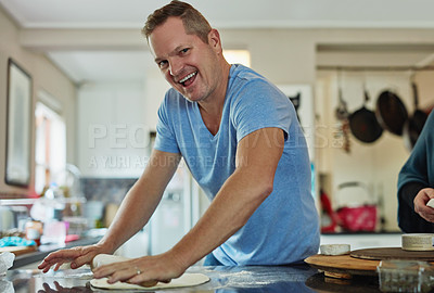 Buy stock photo Cropped portrait of a handsome mature man baking in the kitchen