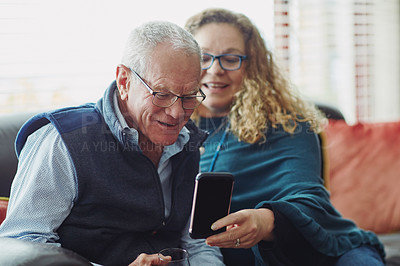 Buy stock photo Cropped shot of a mature woman taking selfies with her senior father at home