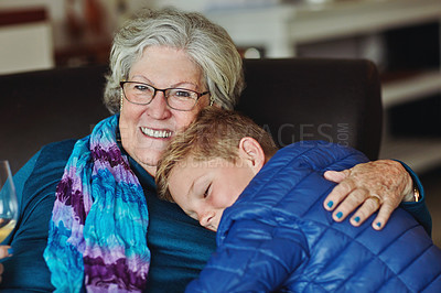 Buy stock photo Cropped portrait of a senior woman sitting on the sofa with her young grandson