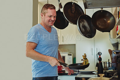 Buy stock photo Cropped shot of a handsome mature man cooking in the kitchen at home
