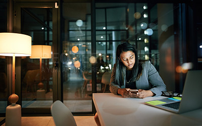 Buy stock photo Shot of a young businesswoman using her cellphone while working late