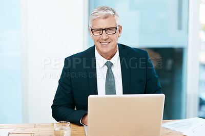 Buy stock photo Cropped portrait of a handsome mature businessman working on his laptop in the office
