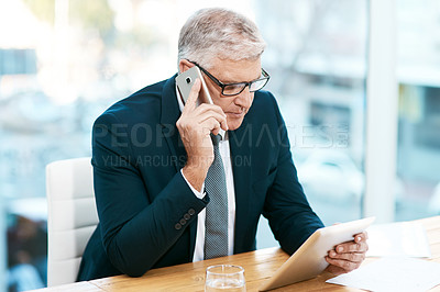 Buy stock photo Cropped shot of a handsome mature businessman working on his tablet while making a phonecall in the office