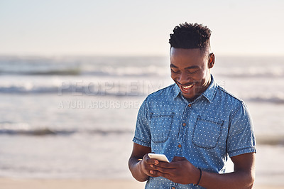 Buy stock photo Shot of a happy young man using a mobile phone at the beach